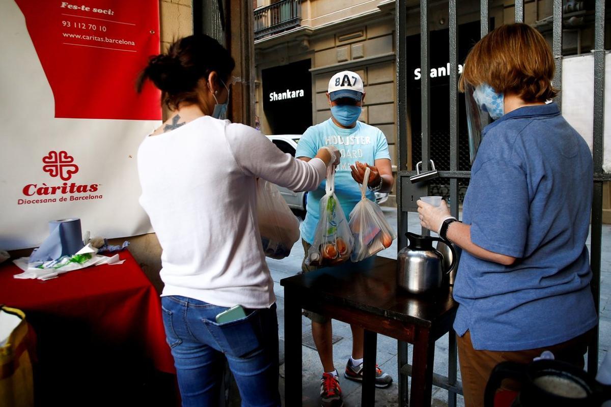 Voluntarios de la parroquia de Santa Anna de Barcelona reparten comida para más de 200 personas.