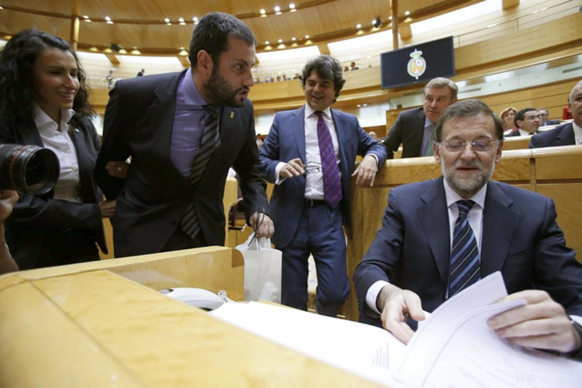 El senador Ibán García entrega un casco minero, en una bolsa,a Mariano Rajoy.