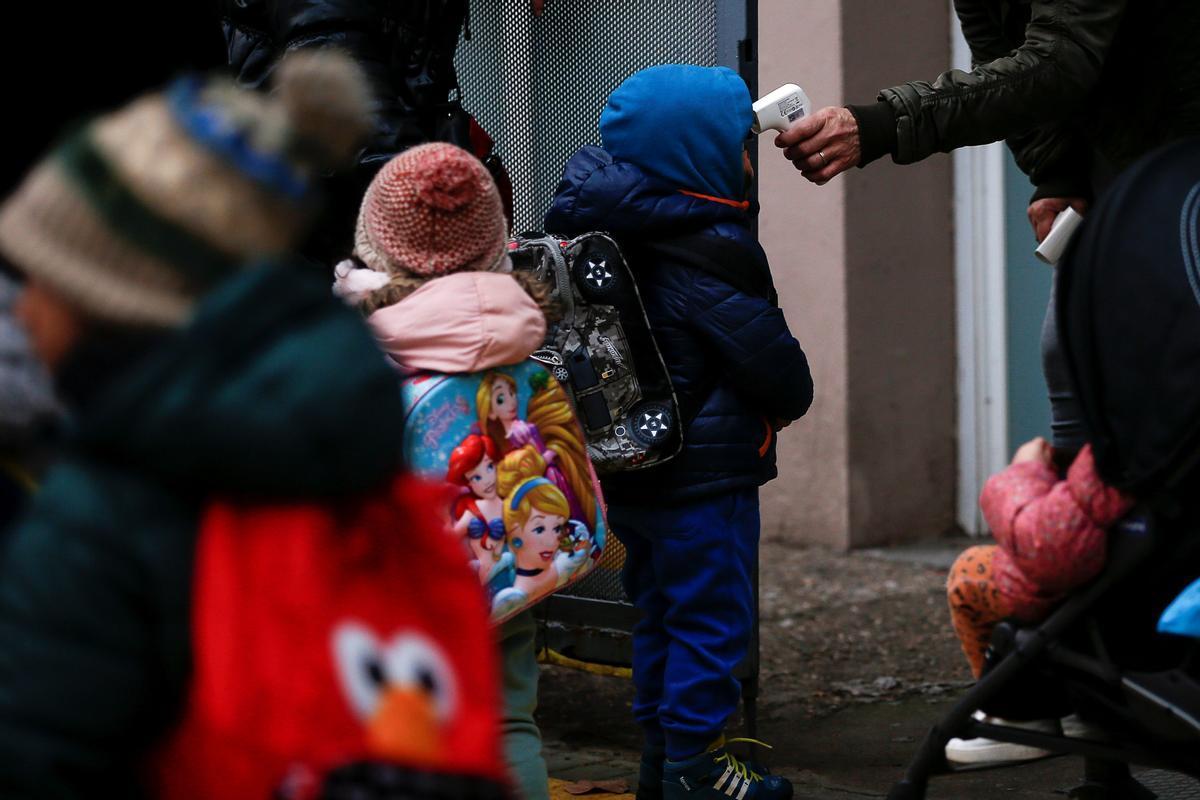 Una profesora toma la temperatura a un alumno de la Escuela Rubén Darío de Barcelona, en la vuelta al cole tras las vacaciones de Navidad.