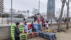 Alumnos del colegio La Farigola del Clot se asoman hacia el patio del instituto vecino, el Salvador Espriu, el pasado viernes.