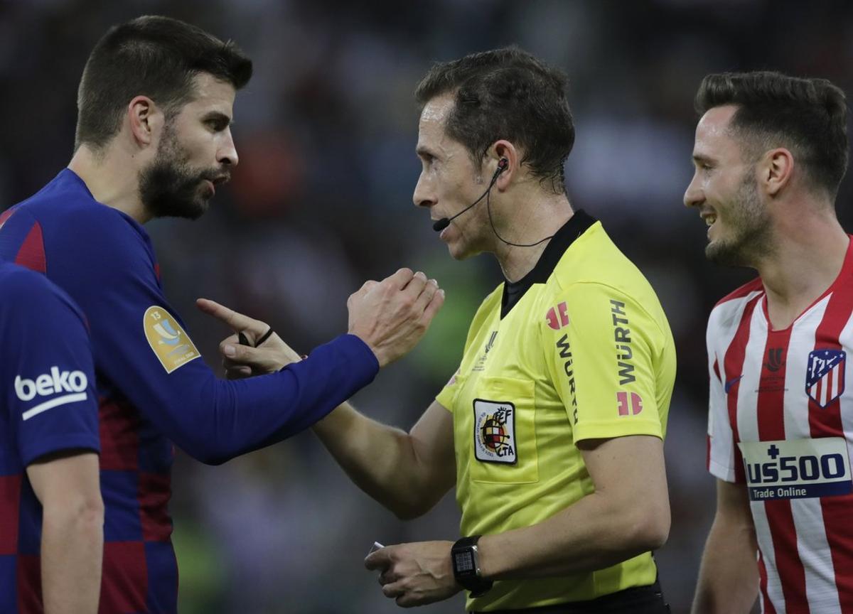 El barcelonista Piqué (i) protesta ante el colegiado de la semifinal de la Supercopa frente al Atlético.