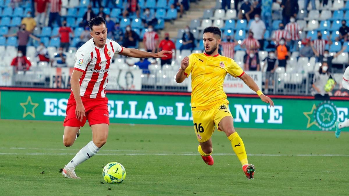 Yan Couto, del Girona, intenta cortar el avance de un jugador del Almería.