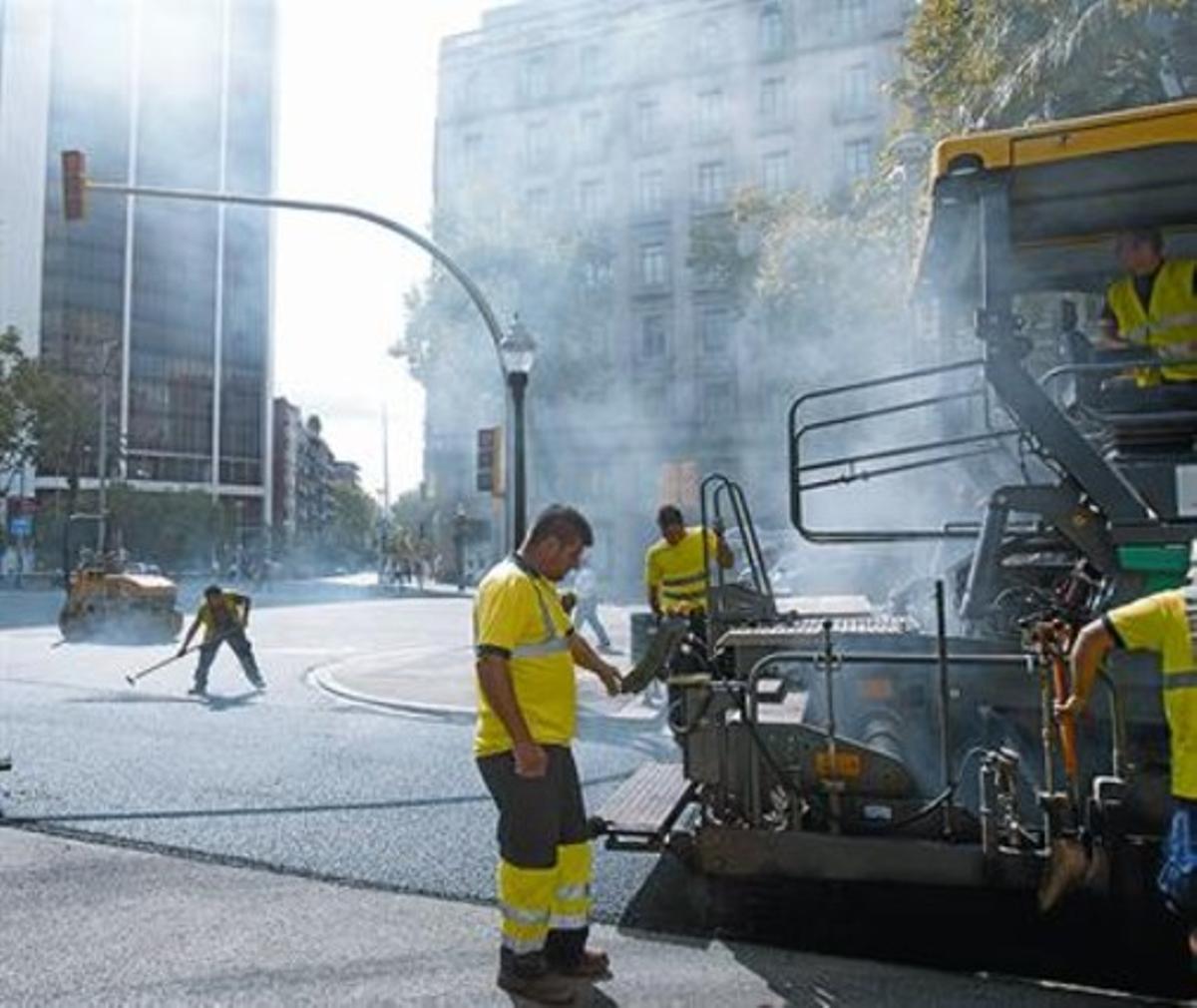 Uns obrers realitzen obres d'asfaltatge en un tram de l'avinguda Diagonal i, a la dreta, imatge del bolcat d'asfalt en un tram del carrer d'Aragó, ahir.