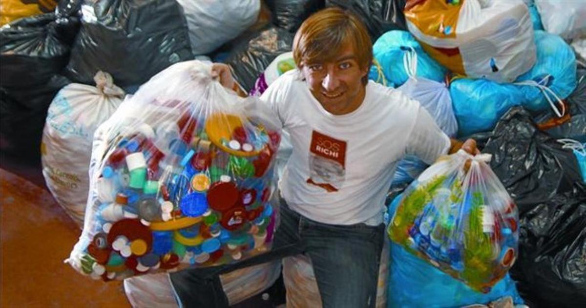 PALAMÓS Un colaborador de la campaña del niño Richi García con sacos de tapas.