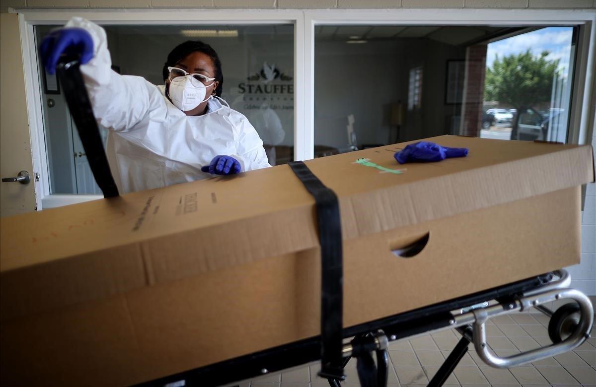 Una operaria del servicio de la funeraria prepara una caja con uncadáver para su posterior cremación.