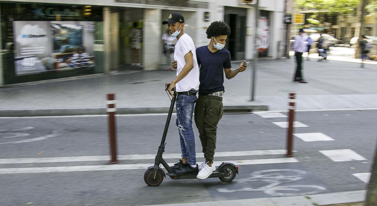 Dos jóvenes circulan en patinete eléctrico por el carril bici de Gran Vía, en Barcelona.