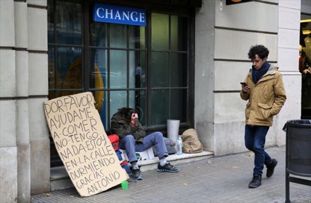 Un sintecho pide ayuda en una calle de Barcelona.