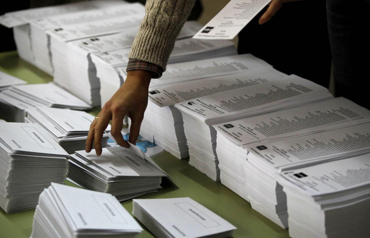 Una persona agafa una papereta de vot en un col·legi electoral de Madrid.