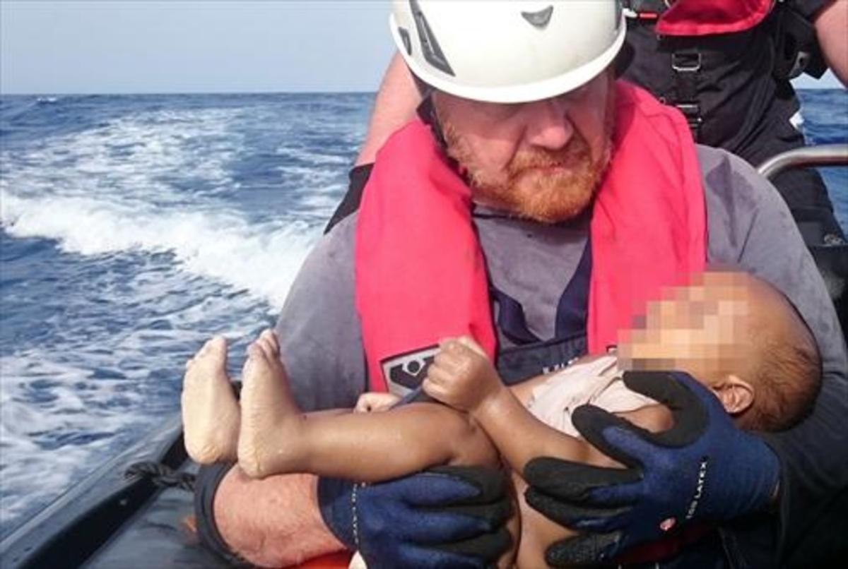 Un voluntario de Sea Watch sujeta el cadáver de un bebé ahogado a finales del pasado mayo tras un naufragio en el Mediterráneo.