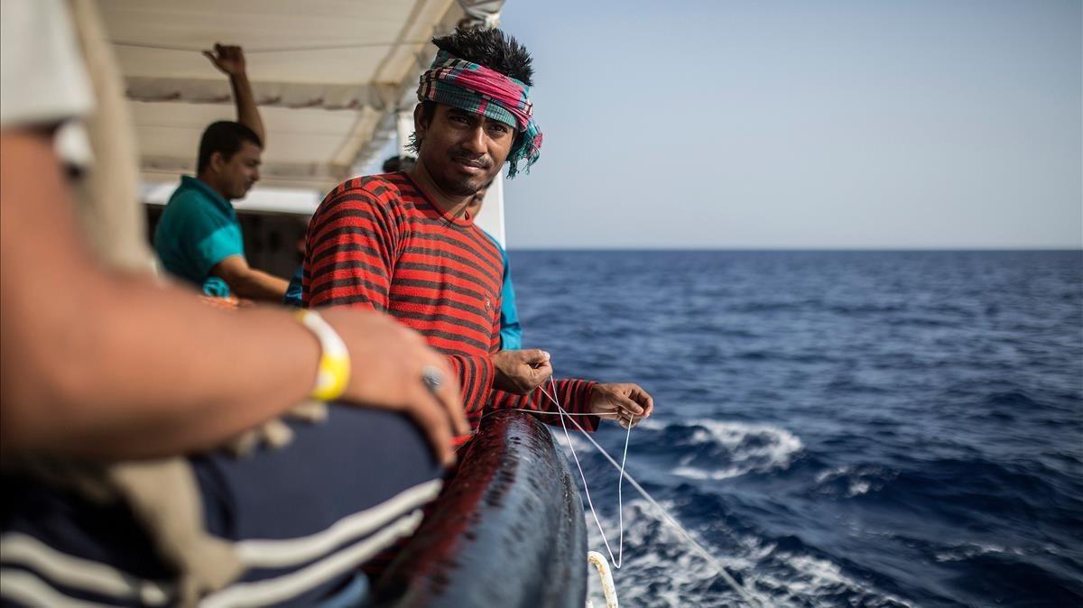 Uno de los migrantes que viajan en el Open Arms tratando de pescar, hoy domingo.