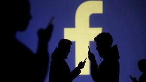 FILE PHOTO  Silhouettes of mobile users are seen next to a screen projection of Facebook logo in this picture illustration taken March 28  2018  REUTERS Dado Ruvic File Photo