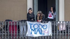 'Todo mal', la queja de tres jóvenes desde su balcón del Eixample, en Barcelona, durante la pandemia.