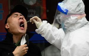 Un médico realiza un test de coronavirus en Wuhan, China.