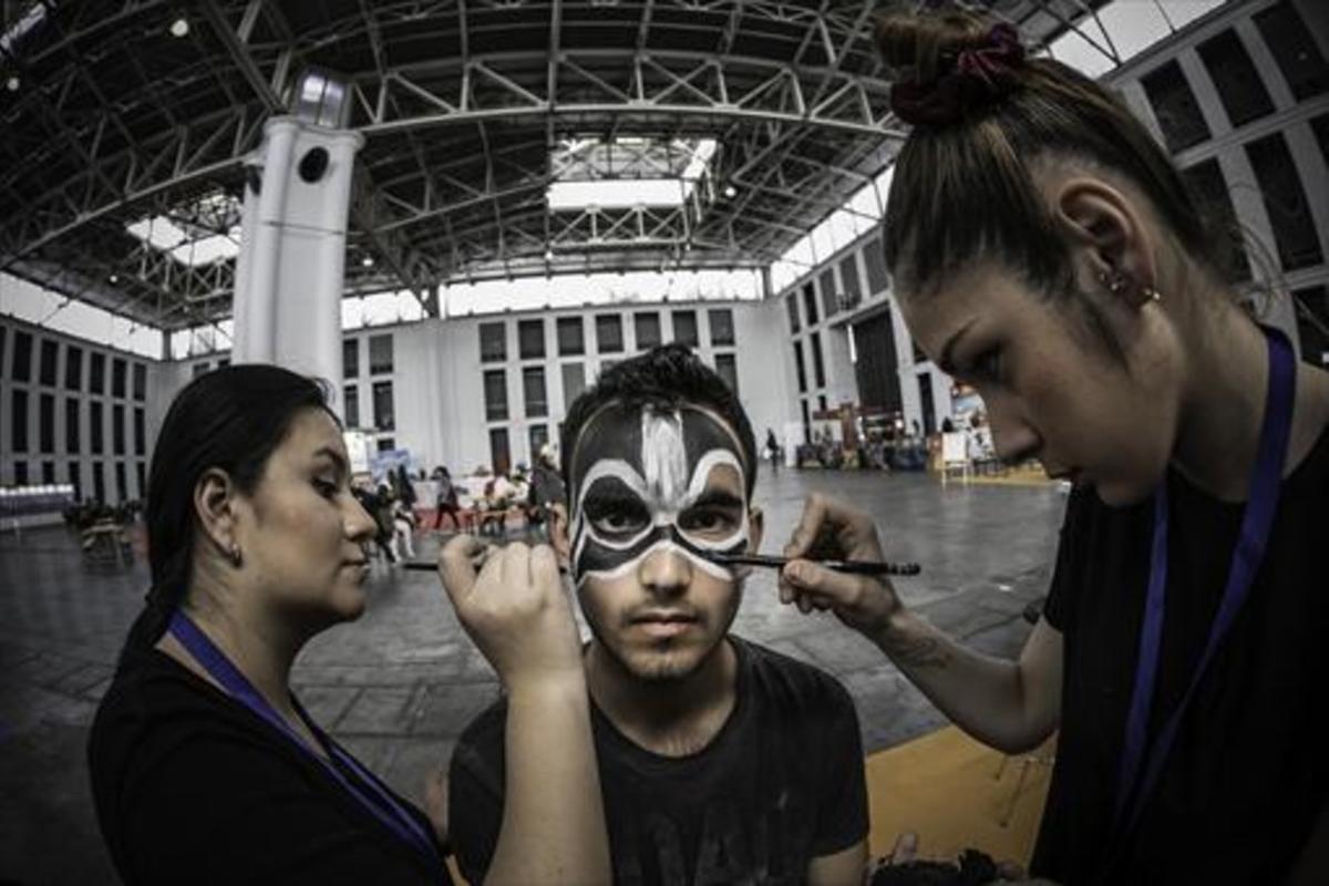 Dos monitoras maquillan a un joven visitante del Saló del Cómic, que se celebra en el recinto ferial de Montjuïc.