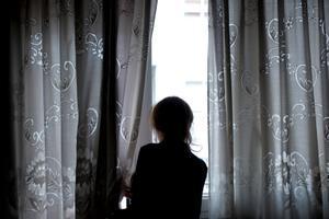 Una mujer mira por la ventana, en abril del 2020, en pleno estado de alarma en España.