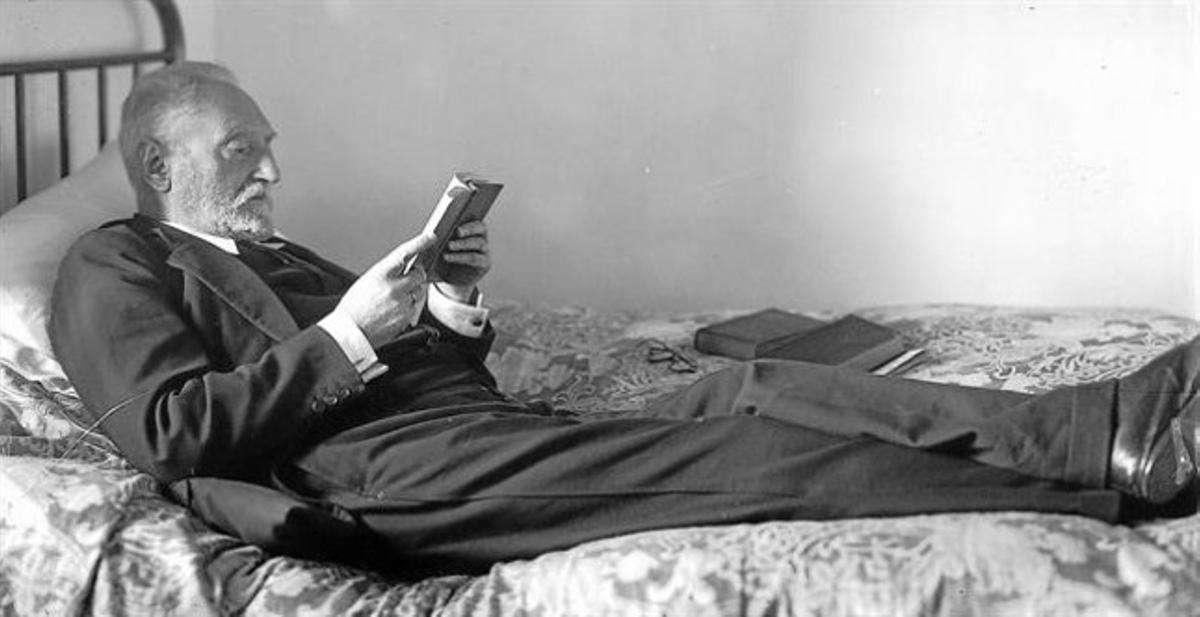 Miguel de Unamuno, con estudiada pose, lee tendido en la cama, en su domicilio de la calle de Bordadores, en Salamanca.