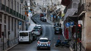 Una de las calles de Lisboa completamente vacía, solo con un coche patrulla de la policía, durante el toque de queda.