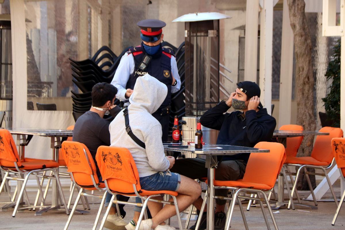 Un agente de los Mossos pide a unos clientes de una terraza de un bar en la plaza de la Font de Tarragona que se pongan la mascarilla mientras no consumen productos.