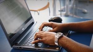 Un hombre teclea en un ordenador portátil.