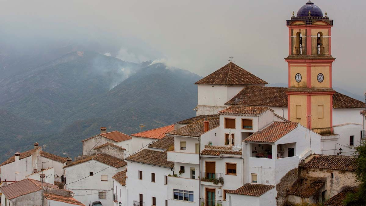 Controlado el incendio forestal de Sierra Bermeja (Málaga). En la foto, la localidad de Algatocín, con columnas de humo al fondo.