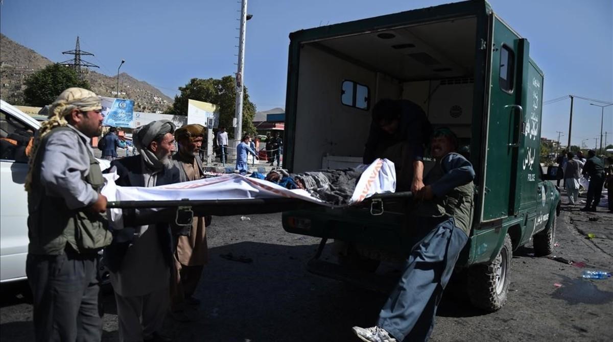Voluntarios afganos mueven los cuerpos de víctimas del atentado suicida, en Kabul, este sábado.