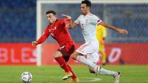 Sergio Busquets y Xherdan Shaqiri pugnan por un balón durante el partido.