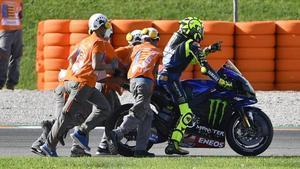 Los comisarios de Cheste ayudan a Valentino Rossi a retirar su Yamaha averiada.
