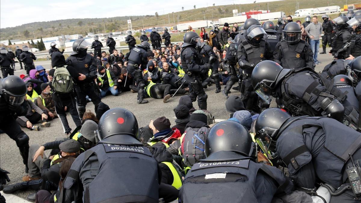 Agentes de la Brimo de los Mossos desalojan por la fuerza la AP-7 a la altura de Figueres.