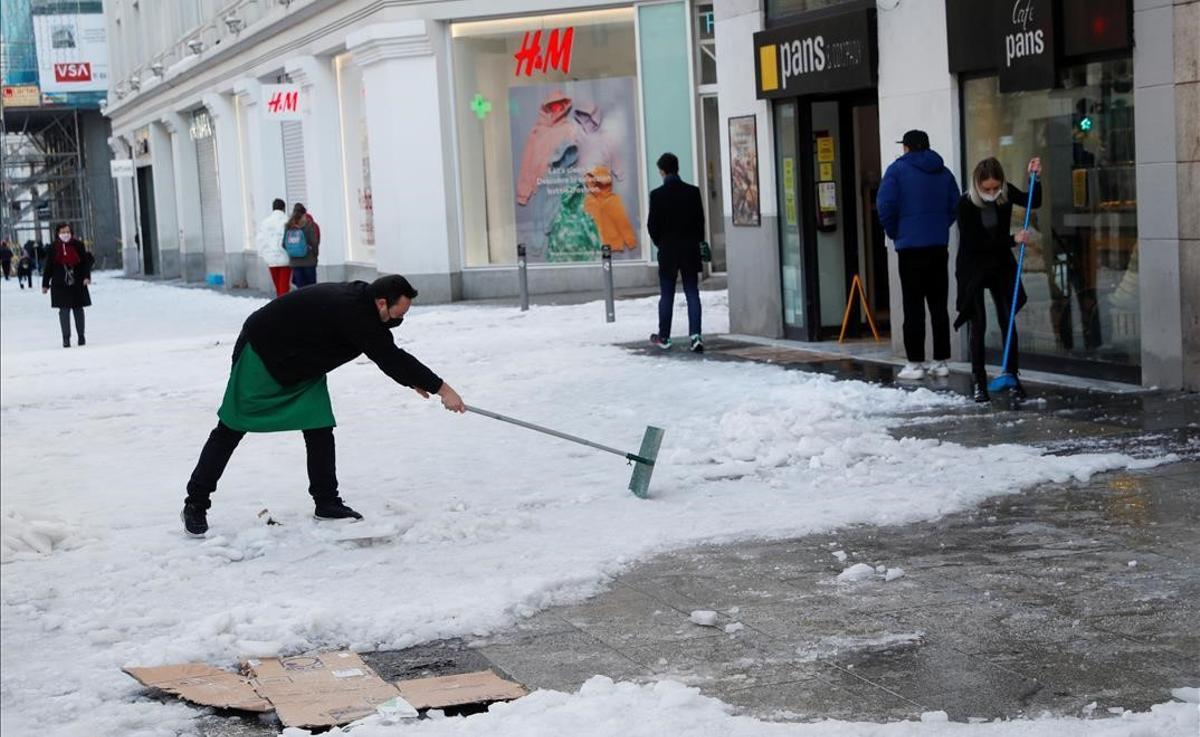Un empleado de un comercio en la Gran Vía de Madrid retira la nieve de la acera, tras la nevada caída el fin de semana.
