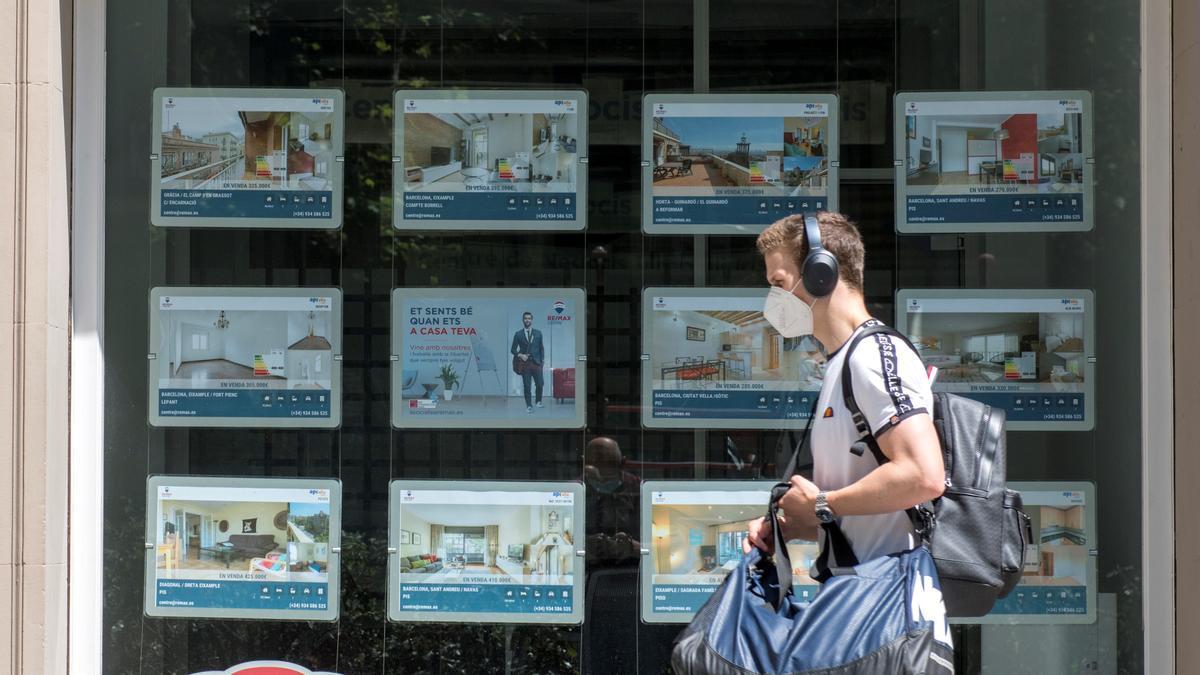 Un joven pasa ante una agencia inmobiliaria.