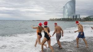 Algunos de los bañistas que se han metido en el mar en la Barceloneta, esta mañana.