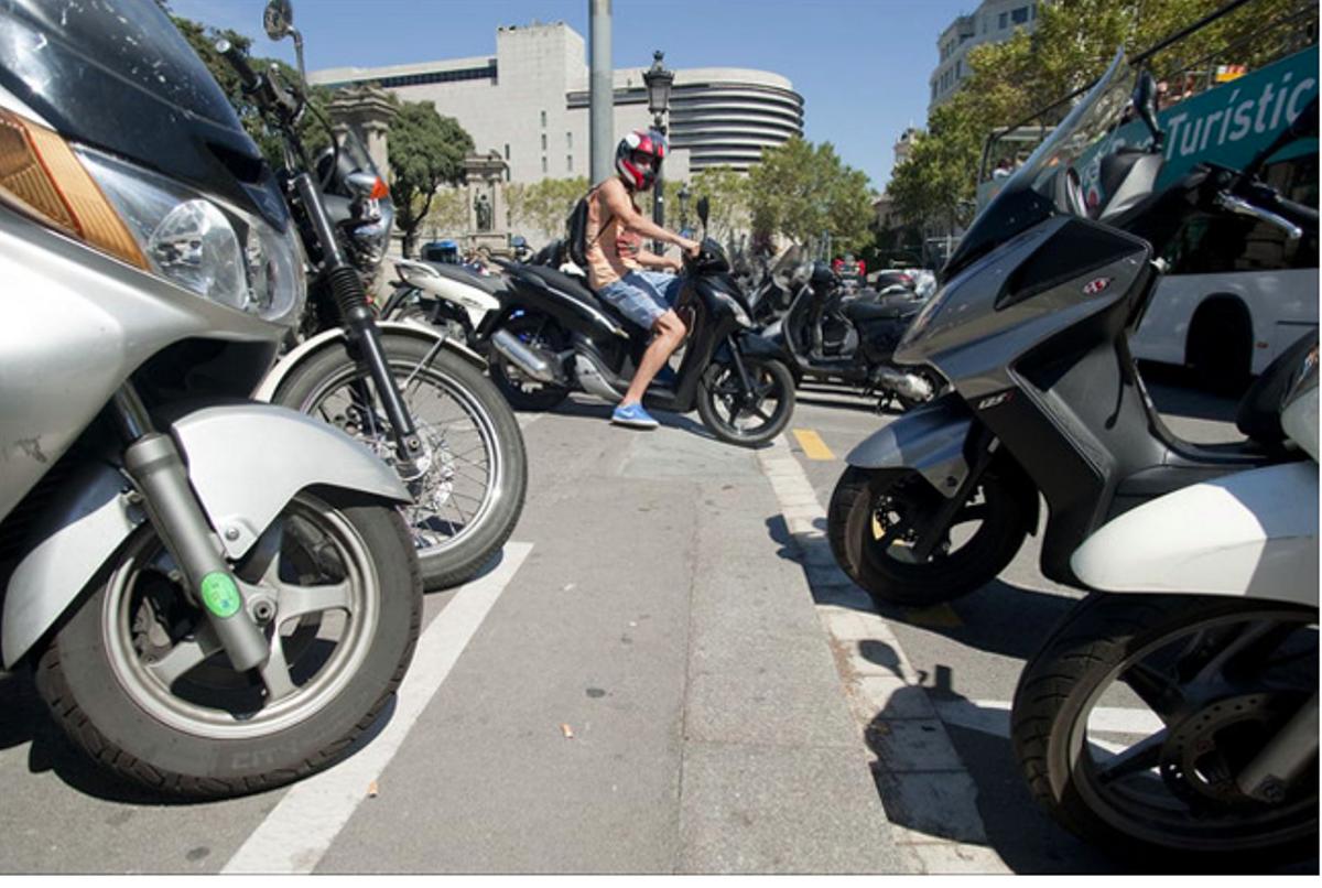 Un motorista intenta aparcar en una zona para vehículos de dos ruedas, en Barcelona