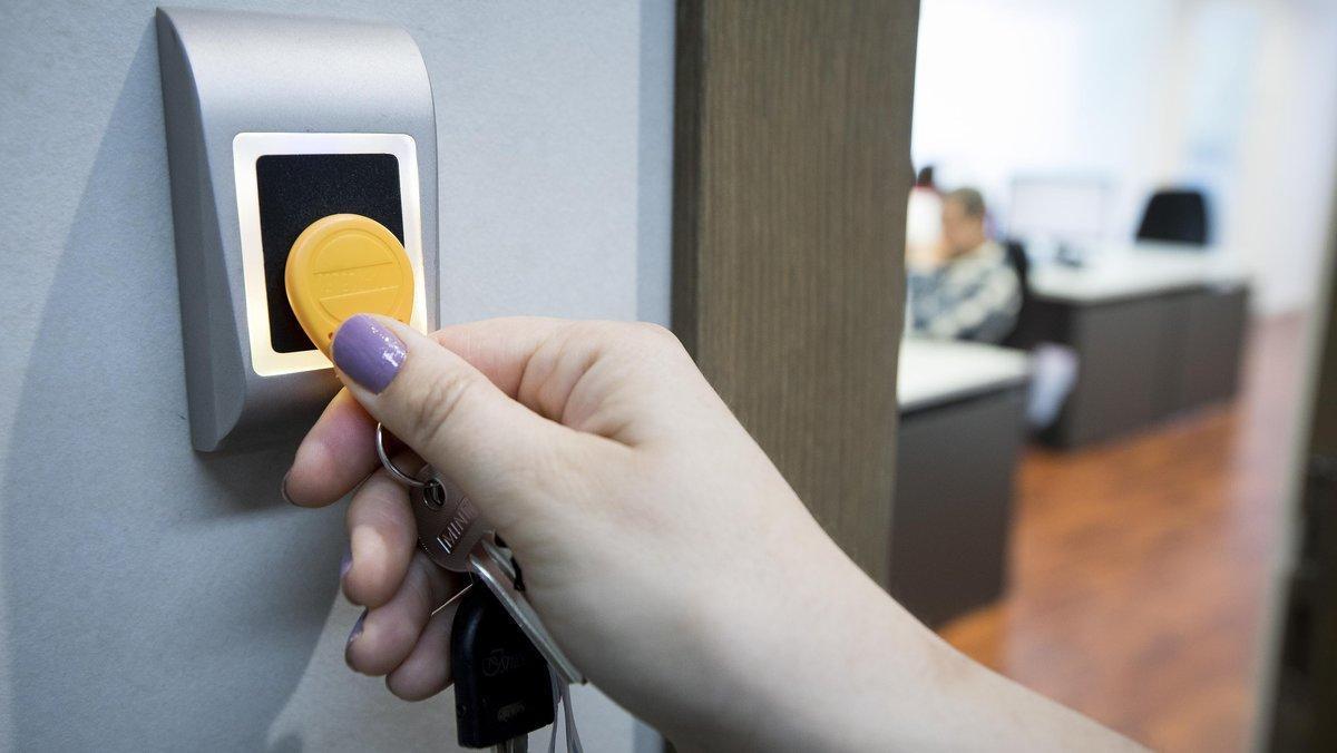 Una empleada utiliza una llave digital para fichar al comenzar y terminar su jornada laboral en unas oficinas.