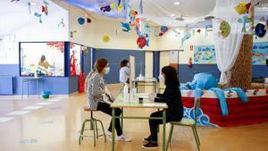 Una administrativa de la Escola L' Estel de Barcelona atiende a una persona durante la preinscripción escolar del año 2020.