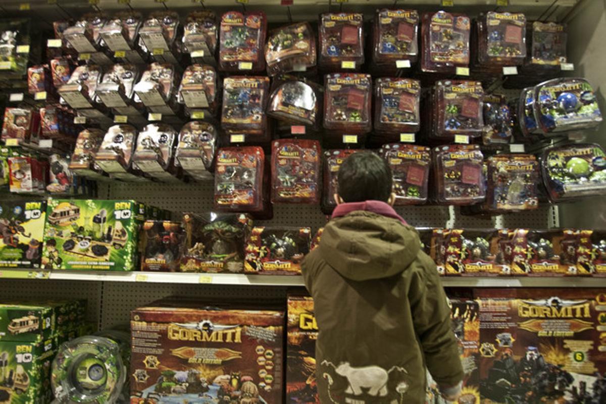Un niño mira una estantería llena de juguetes en una tienda de Barcelona.