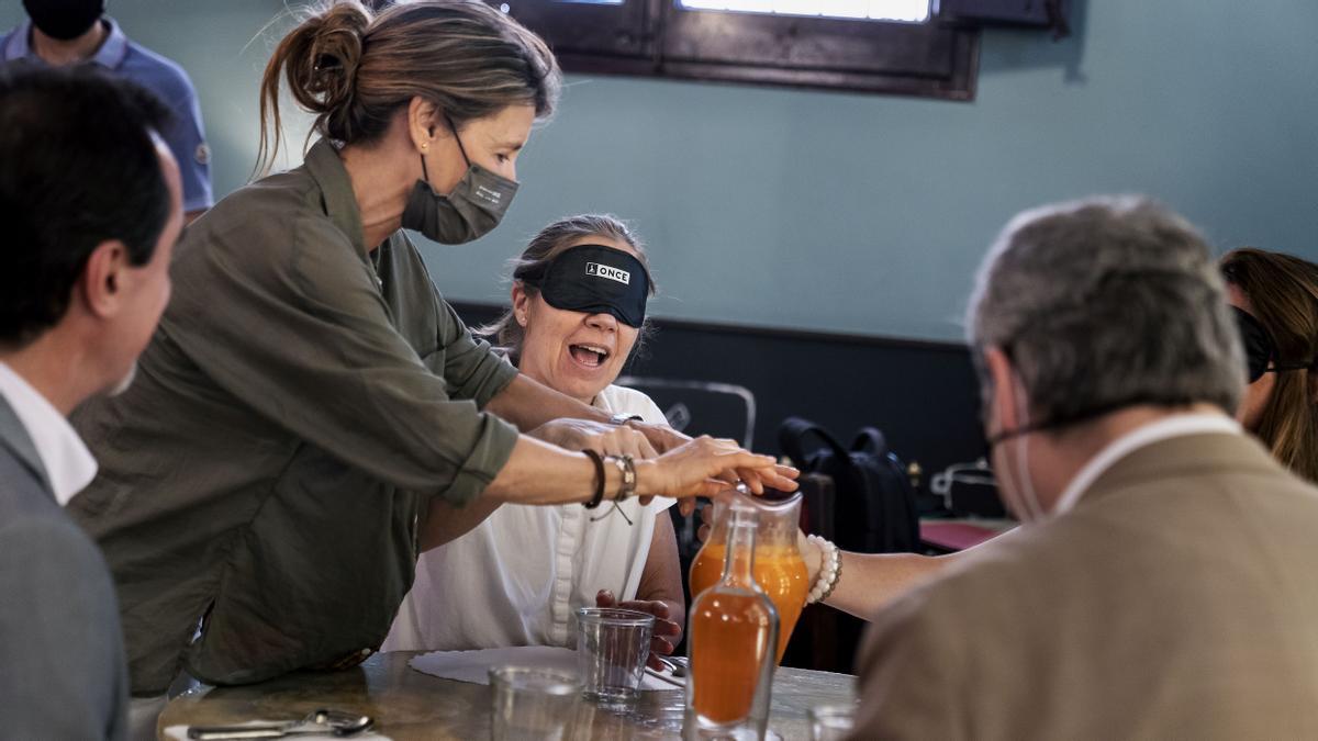 Una técnica de rehabilitación de la ONCE enseña cómo servirse un vaso a la chef Ada Parellada durante una demostración para enseñar a atender a personas ciegas que se ha hecho en el restaurante Semproniana.