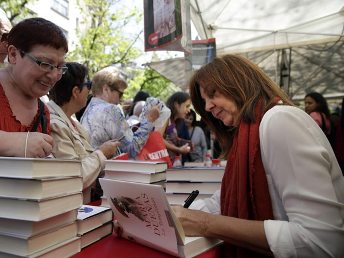 La escritora María Dueñas firma un libro en una de las paradas instaladas con motivo de la Diada de Sant Jordi.
