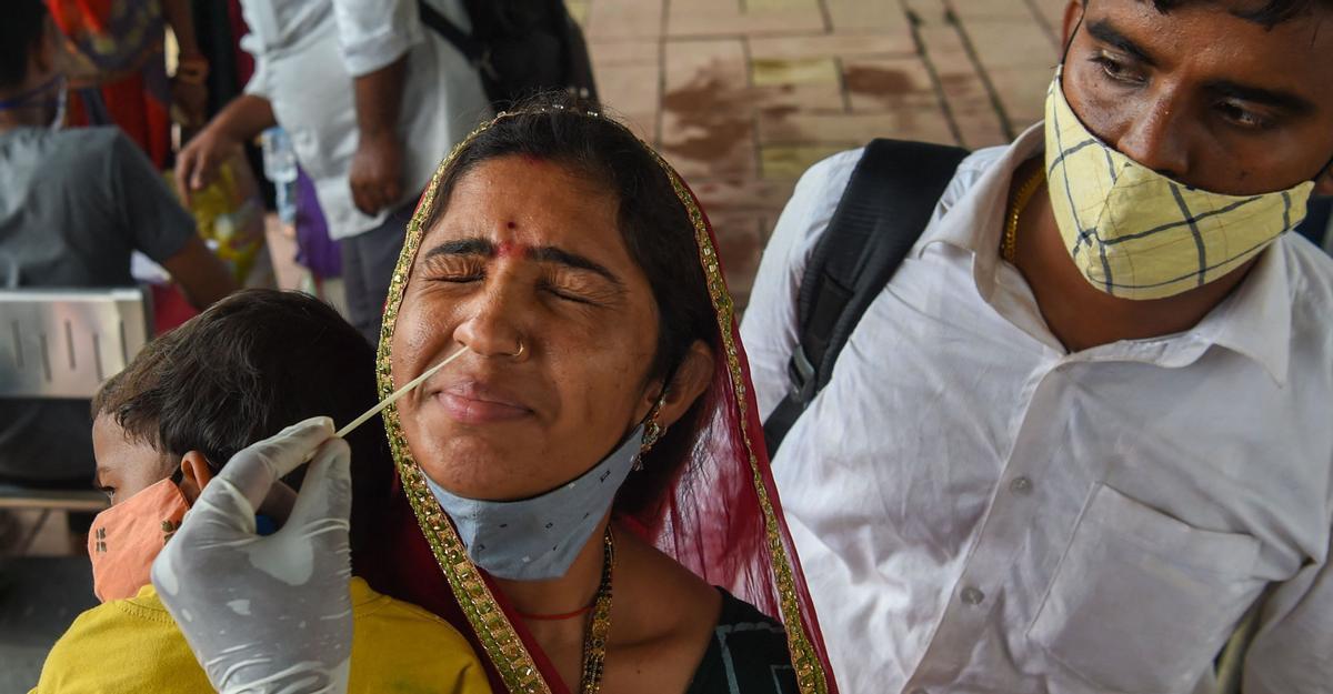Una sanitaria hace una PCR a una mujer tras bajarse de un tren de larga distancia en Mumbai (India), el 9 de julio.
