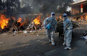 Personal sanitario prepara una pira funeraria en Nueva Delhi.