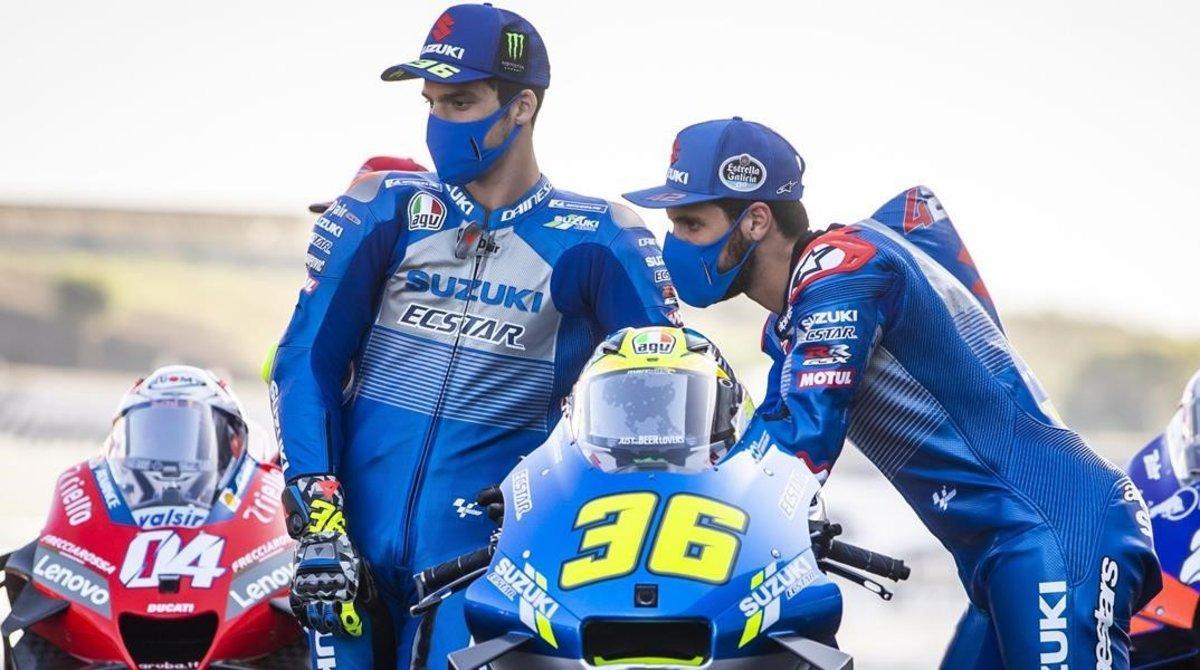 Joan Mir y Alex Rins observan, hoy, en Portimao (Portugal), la moto de un compañero.