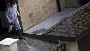 Un hombre con mascarilla limpia el patio de su casa en Sofía, este domingo.