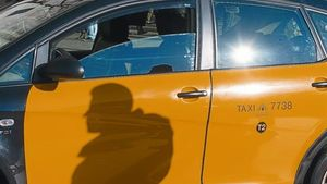 La sombra de un taxista se refleja sobre su vehículo, en cuya puerta figura el identificador del turno T2, el pasado sábado.