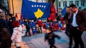 Ciudadanos de Pristina pasean ante banderas de Kosovo y Albania, ayer.