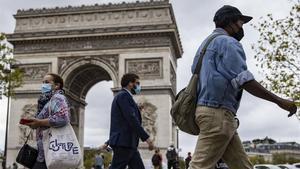 Parisinos con mascarilla caminan por los Campos Elíseos, con el Arco de Triunfo detrás.