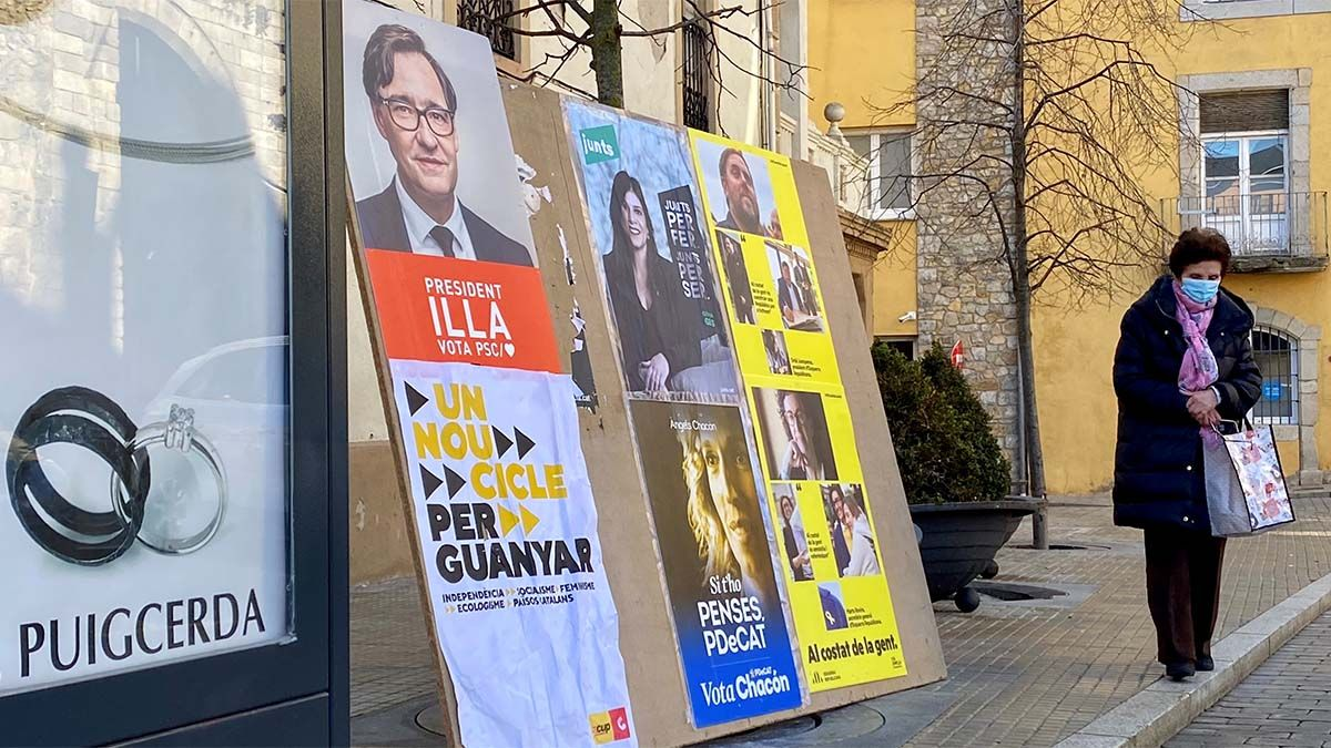 Una mujer, ante unos carteles de las elecciones catalanas del 14 de febrero.