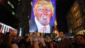 Una mujer enarbola una pancarta con una caricatura de Trump durante una manifestación contra el presidente estadounidense en Nueva York, en el 2016.