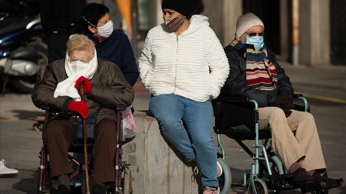 Dos mujeres mayores con sus cuidadoras, en la plaza de la Catedral de Barcelona.