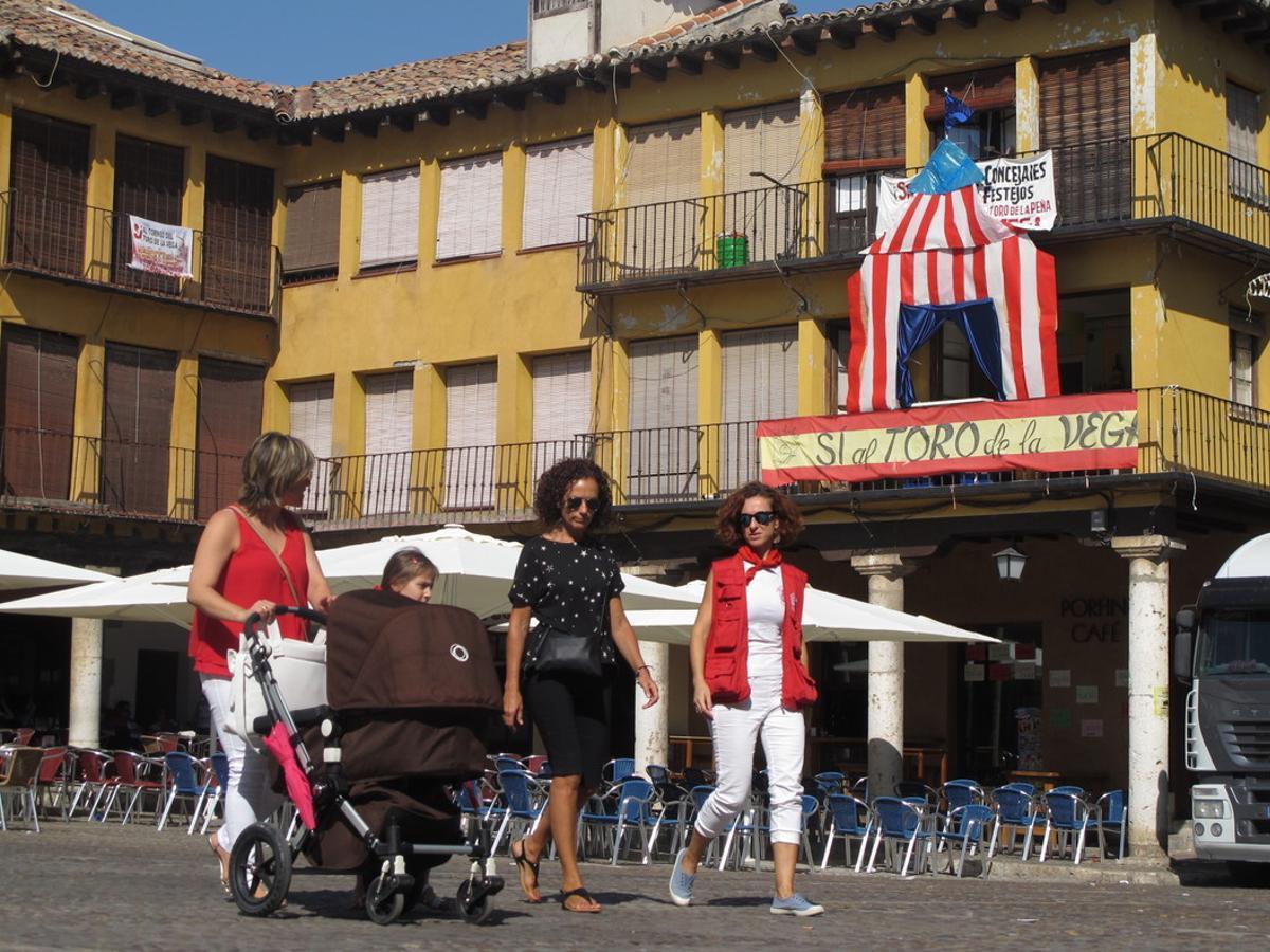 Una familia pasea por la plaza Mayor de Tordesillas. En un balcón, defensa a ultranza del Toro de la Vega.