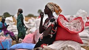 Una habitante de una aldea de Sudán del Sur que se había ofrecido como voluntario para recoger raciones de alimentos en el lugar de un lanzamiento aéreo se toma un descanso.