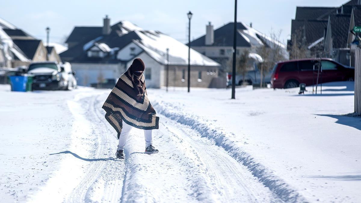 Una persona camina entre la nieve, cubierta con una manta, en Pflugerville, en Texas.